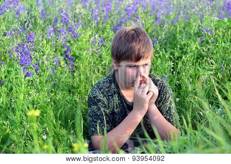 Teen Boy With Allergies In Flowering Herbs