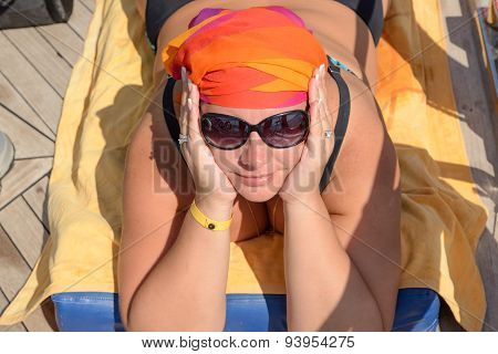 Young Woman Is Lying On Her Stomach For Tanning.