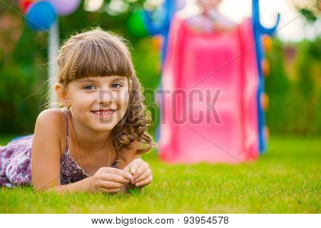 Pretty Girl Lying On Grass At Playground