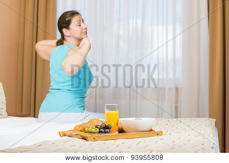 Girl Stretching After Sleep Sitting On A Bed
