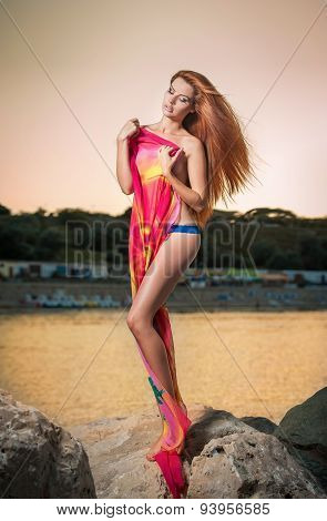 Beautiful woman with red and yellow large veil posing on the beach at sunset in a hot summer evening