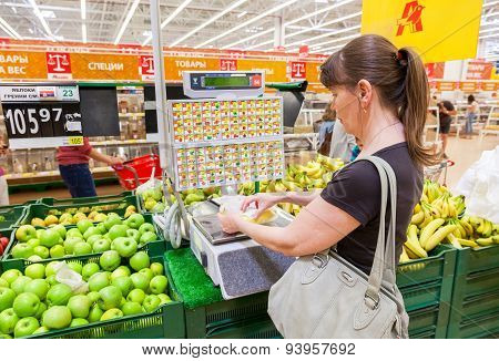 Young Woman Weighing Bananas On Electronic Scales In Produce Department Of The Auchan Store