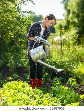 Cute Girl Watering Plants In Garden At Hot Sunny Day