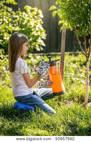 Brunette Girl Working In Garden With Fertilizing Spray
