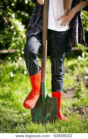Girl In Red Rubber Boots Holding Leg On Shovel At Garden