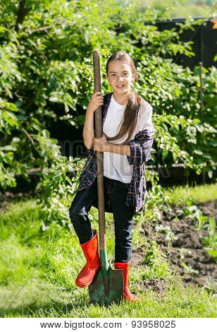 Smiling Girl In Red Gumboots Digging Soil At Garden