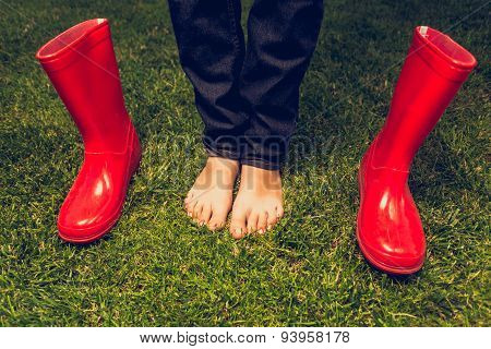 Toned Photo Of Barefoot Girl Posing With Red Gumboots On Meadow