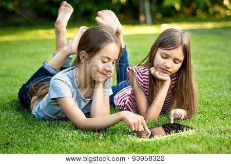 Two Sisters Lying On Grass Outdoors And Playing On Digital Tablet