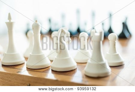 Closeup Of White Chess Piece Set On Wooden Board