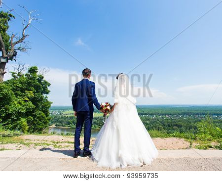 bride and groom standing back