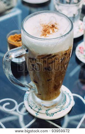 Frothy, layered cappuccino in a clear glass