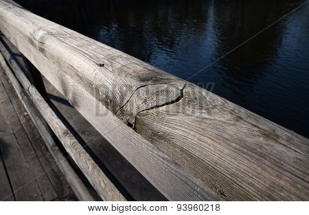 Wooden Bridge Handrail Diagonal Shot With Blue Water Background