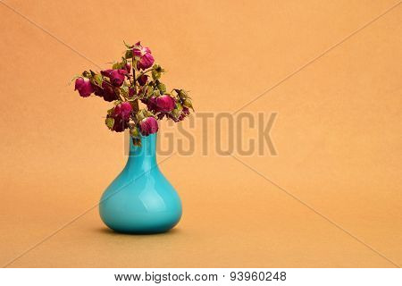 Dried-up Red Roses Bouquet In A Blue Vase On Background Of Kraft Paper