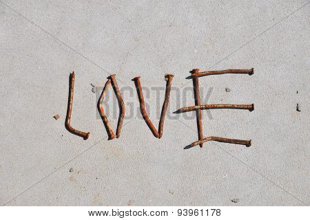 Love Word Formed By Rusty Nails At Grey Concrete Background