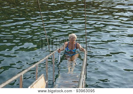 Senior Woman In Water Is Holding Handrails Of Gangplank.