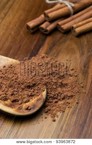 Cocoa Powder With Cinnamon Sticks On A Wooden Table
