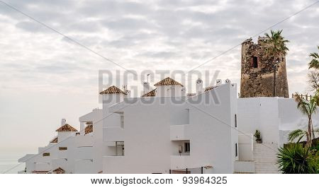 Rooftops Of The Spanish Condominium And Tower Against Cloudy Sky