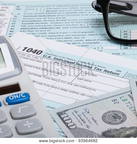 Us 1040 Tax Form, Calculator, Glasses And Dollars - Studio Shot