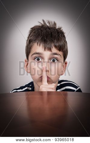 Young boy holding a index finger on his lips
