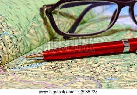Ballpoint pen and glasses lie on geographical atlas