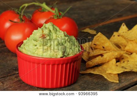 Guacamole dip with corn chips on rustic wooden table