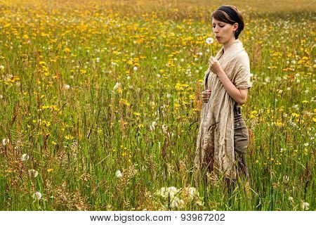 Young Woman With A Dandelion In A Colorful Wildflower Meadow