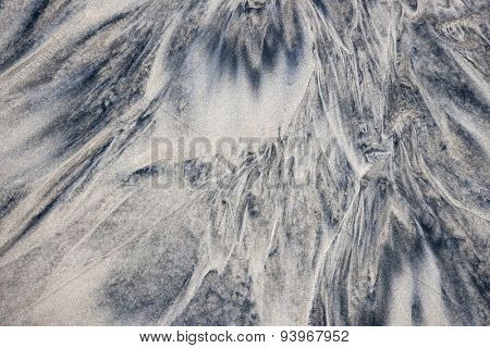 Grey and beige abstract background of wet sand texture formed by flowing water on beach