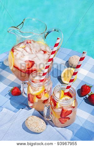 Ice cold homemade strawberry lemonade in jug and glasses with paper straws on outdoor summer pool side table