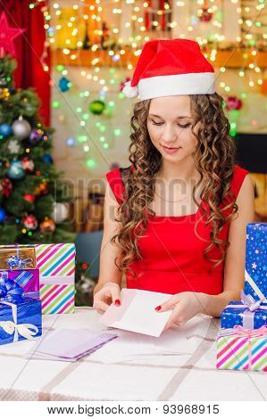 She Puts A Postcard With Christmas Greetings In An Envelope