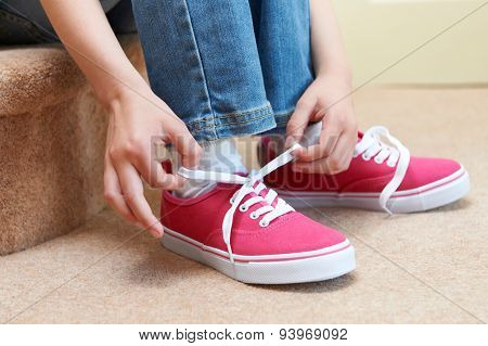 Girl Sitting On Stairs And Tying Shoelaces