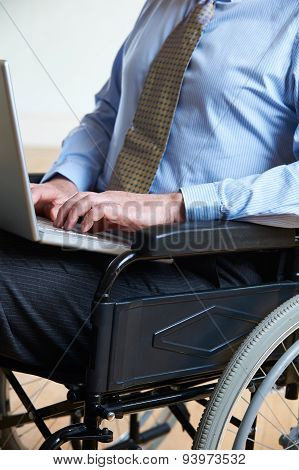 Disabled Businessman In Wheelchair Using Laptop