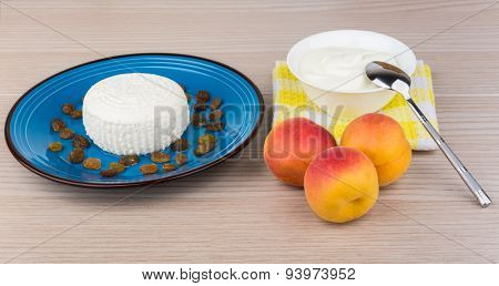 Curd And Raisins In Plate, Sour Cream, Spoon And Peaches