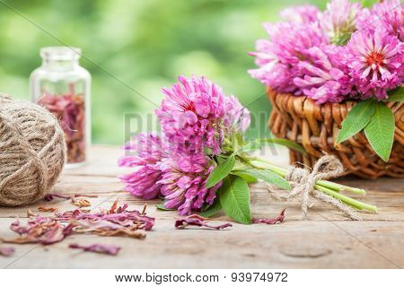 Bunch Of Clover And Basket With Flowers On Wooden Table.