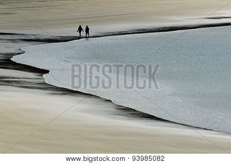 Silhouette of a couple walks in a secluded beach.