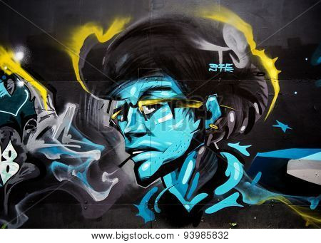 MOSCOW - JUNE 21, 2015: Graffiti on a urban wall (near B. Novodmitrovskaya street). Smoking man in glasses.