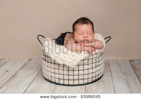 Newborn Baby Boy Sleeping In A Wire Basket