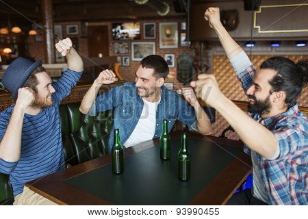 people, leisure, friendship and bachelor party concept - happy male friends drinking bottled beer and raised hands at bar or pub