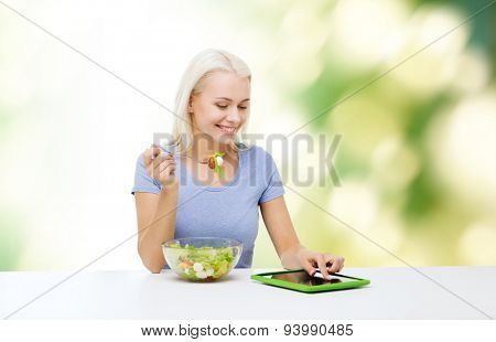 healthy eating, dieting and people concept - smiling young woman with tablet pc computer eating vegetable salad over green natural background