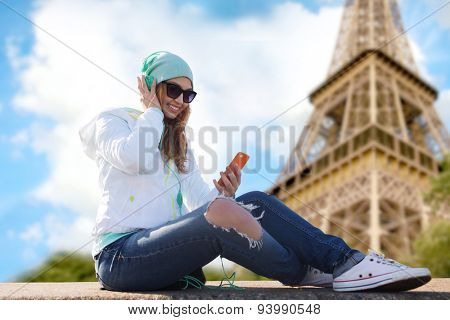 technology, travel, tourism and people concept - smiling young woman or teenage girl with smartphone and headphones listening to music over eiffel tower background