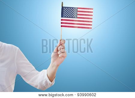 independence day, celebration, patriotism and holidays concept - close up of woman holding american flag in hand at 4th july party over blue background