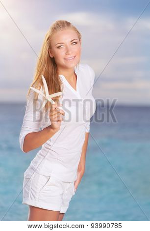 Pretty girl on the beach in sunny day with starfish in hand, wearing cute white beach clothes, having fun on tropical resort on Maldives