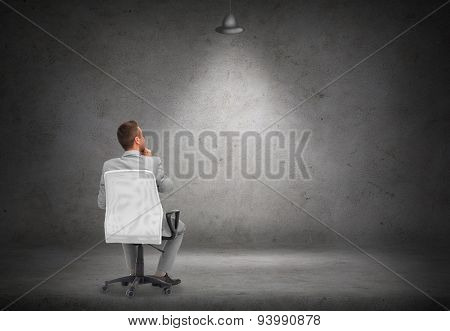 business, people and advertisement concept - businessman in suit sitting in office chair over blank white board or screen on gray wall background from back