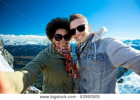 tourism, travel, people, leisure and technology concept - happy international teenage couple taking selfie over alps mountains in austria background