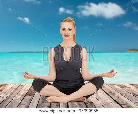 people, health, wellness and meditation concept - happy young woman meditating in yoga lotus pose on wooden floor over sea and blue sky background