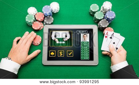 casino, online gambling, technology and people concept - close up of poker player hands with playing cards, tablet pc computer and chips at green casino table