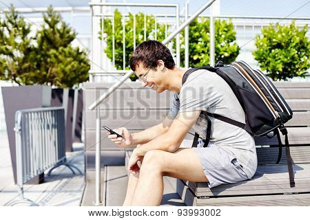 Young joyful man in glasses with backpack and mobile phone sitting on bench and reading message