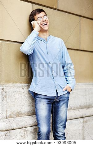 Toothy smiling young man in glasses and blue shirt standing against stone wall with hand in pocket of jeans talking on cell phone