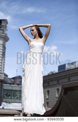 Full length portrait of beautiful model woman with long legs wearing white dress posing summer street