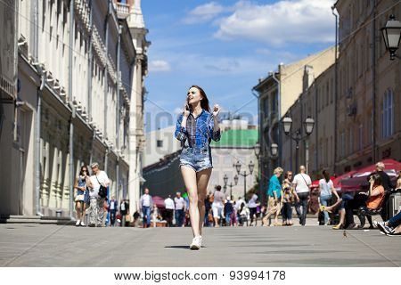 Portrait of young beautiful brunette woman in blue jeans short calling by phone and walking in summer street