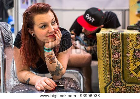 KRAKOW, POLAND - JUNE 6, 2015: People make a tattoos at the 10-th International Tattoo Convention in the Congress-EXPO Center. This year anniversary TattooFest is tattoo Studio with an area of 2000m2.